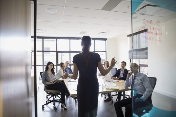 Female business woman leading a meeting in front of her employees.