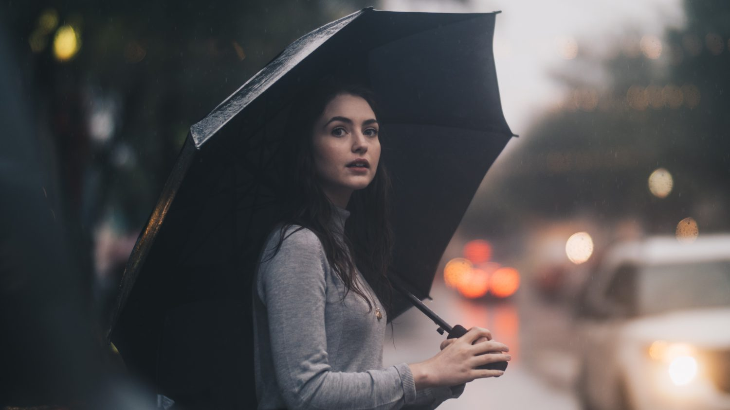 A young white female holding an umbrella, standing in the rain in a vibrant, multicultural city. She has the potential to become a great executive with the correct training and opportunities.