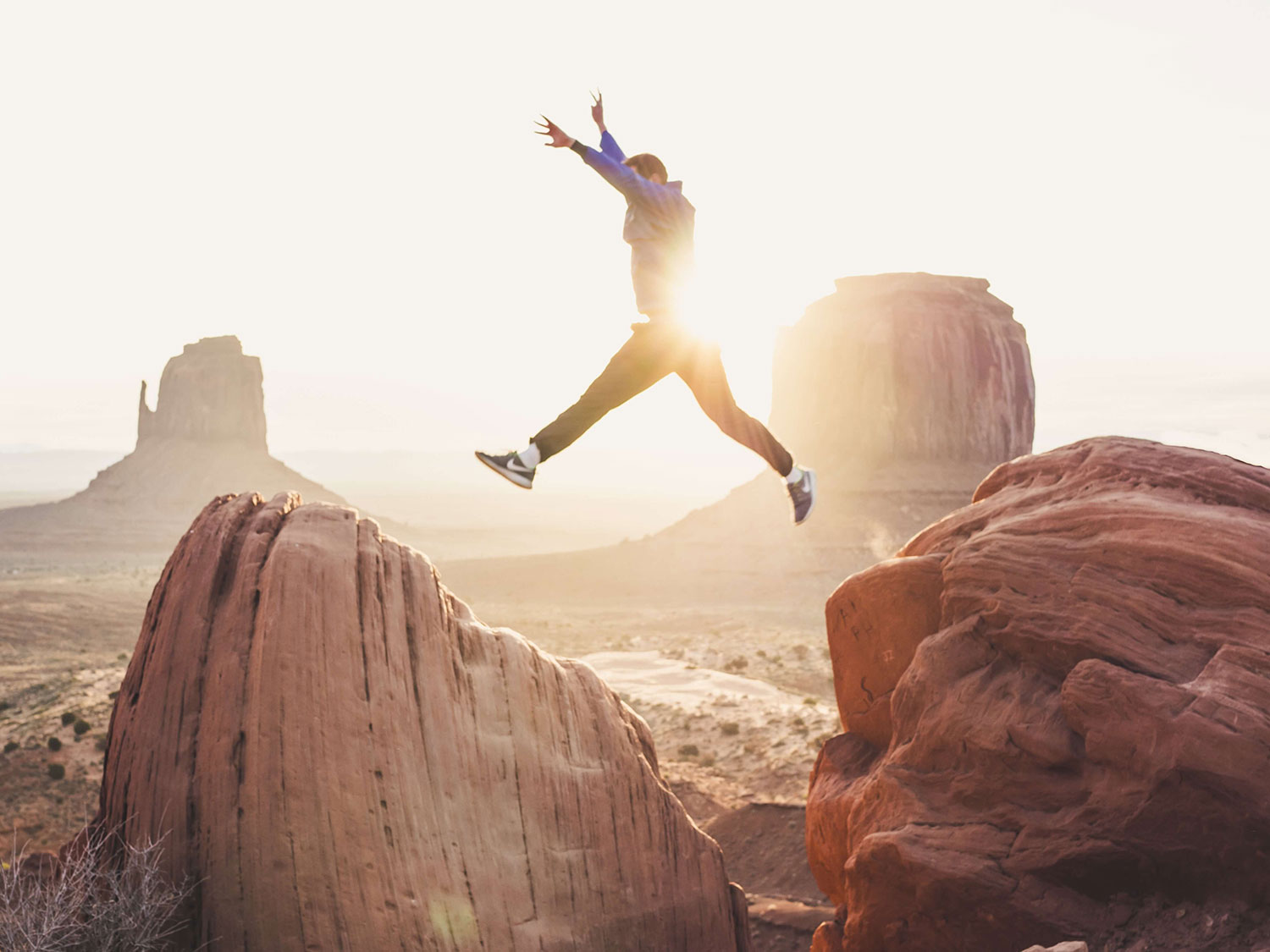 Young man successfully jumping from one rock to another in a mountainous area.